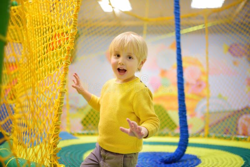 Gelukkig weinig jongen die pret in vermaak in spelcentrum hebben Kind het spelen op binnenspeelplaats stock foto