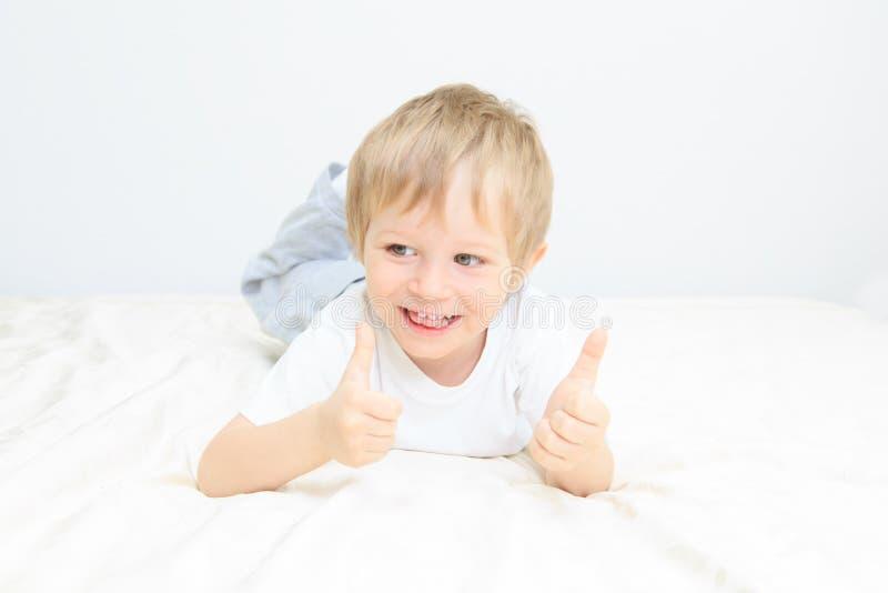 Gelukkig weinig jongen met duimen omhoog op wit royalty-vrije stock afbeeldingen