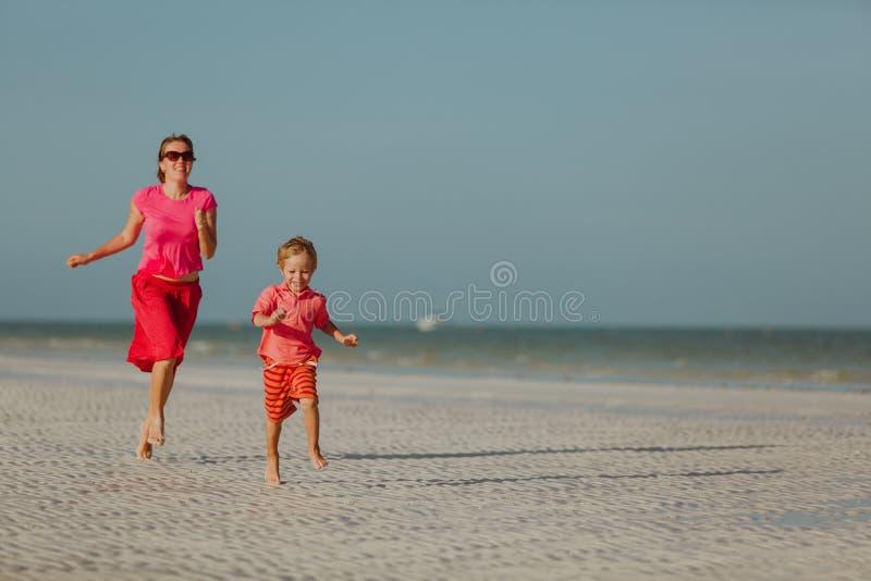 Gelukkig weinig jongen met moeder die op de zomerstrand lopen stock foto