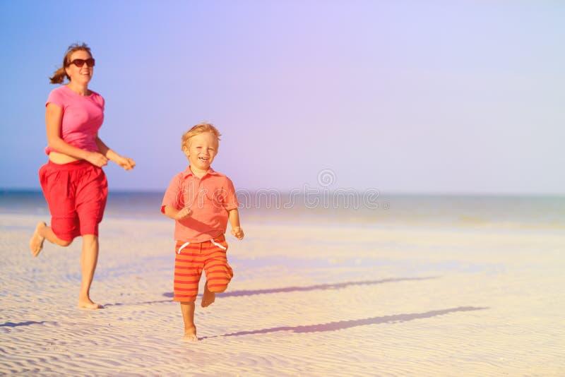 Gelukkig weinig jongen met moeder die op strand lopen royalty-vrije stock foto