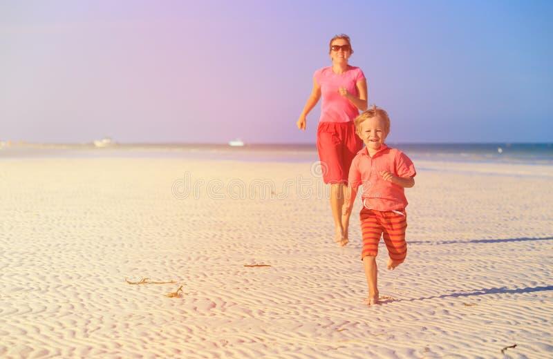 Gelukkig weinig jongen met moeder die op strand lopen stock afbeeldingen