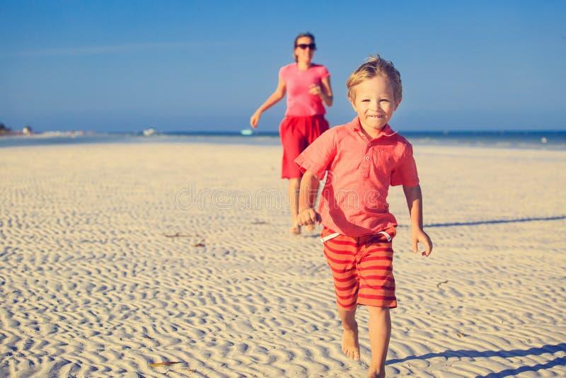 Gelukkig weinig jongen met moeder die op strand lopen royalty-vrije stock afbeeldingen