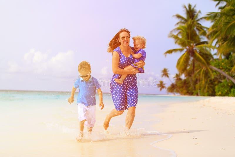 Gelukkig weinig jongen met moeder en zuster die op strand lopen royalty-vrije stock afbeeldingen