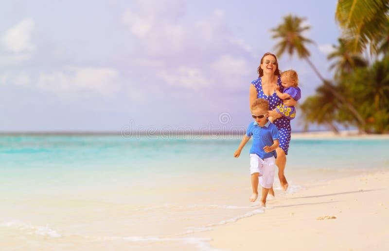 Gelukkig weinig jongen met moeder en zuster die op strand lopen stock afbeelding