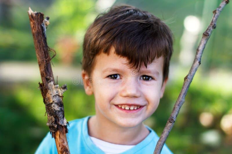 Gelukkig weinig jongen met tak stock fotografie