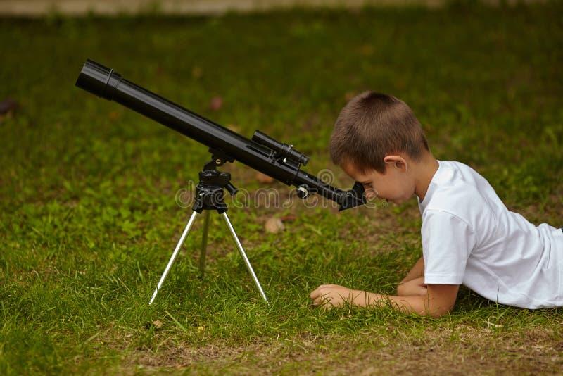 Gelukkig weinig jongen met telescoop stock afbeelding