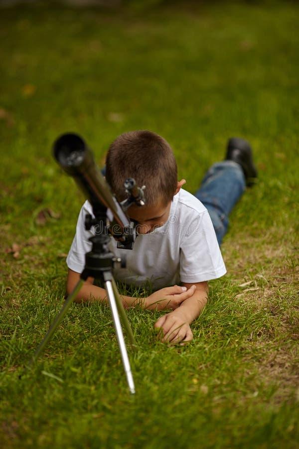 Gelukkig weinig jongen met telescoop stock foto's