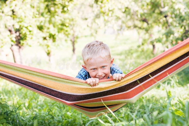 Gelukkig weinig jongen in spelhangmat in de de zomertuin stock foto's