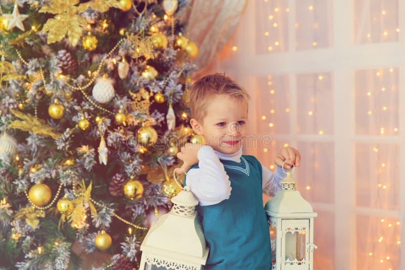 Gelukkig weinig Kerstmislantaarn van de jongensholding in verfraaide woonkamer stock afbeeldingen