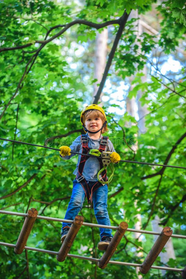 Gelukkig Weinig kind die een boom beklimmen Vroege kinderjarenontwikkeling Avontuur die hoog draadpark beklimmen Kindjongen die p stock foto