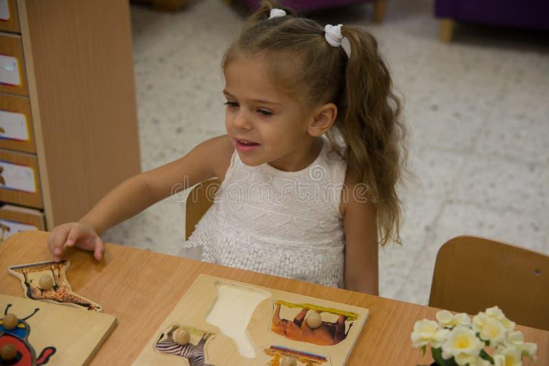 Gelukkig weinig kind, het aanbiddelijke meisje van de blondepeuter, die pret het spelen met puzzel het assembleren stukken van be royalty-vrije stock afbeelding