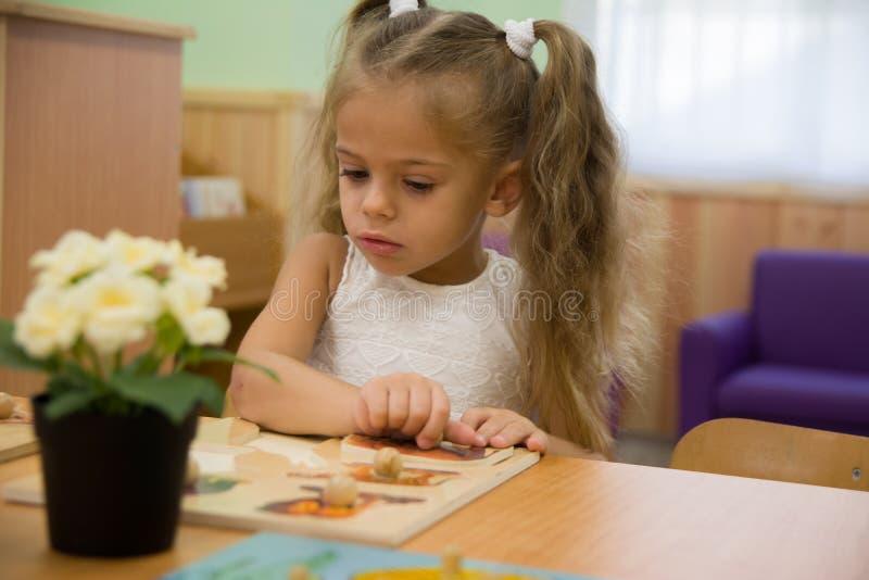 Gelukkig weinig kind, het aanbiddelijke meisje van de blondepeuter, die pret het spelen met puzzel het assembleren stukken van be stock foto