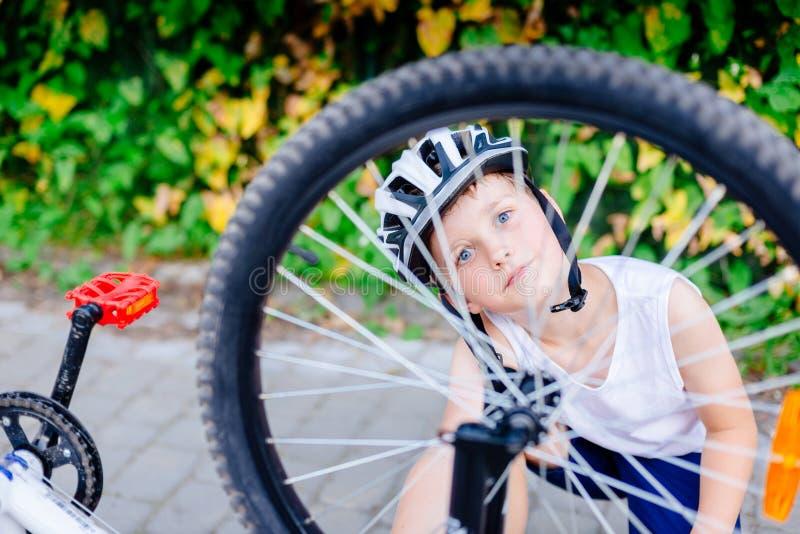 Gelukkig weinig kindjongen die in witte helm zijn fiets herstellen stock foto