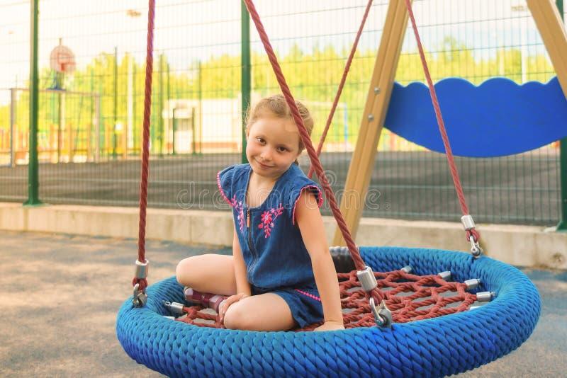 Gelukkig weinig kindmeisje die en op een schommeling in het stadspark lachen slingeren in de zomer royalty-vrije stock afbeelding