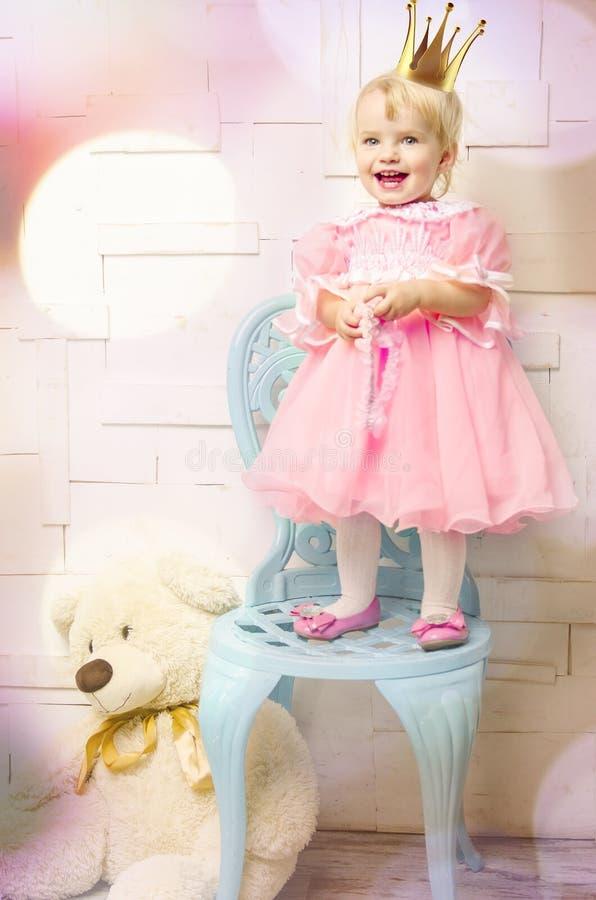 Gelukkig weinig prinses in roze kleding en kroon stock foto's
