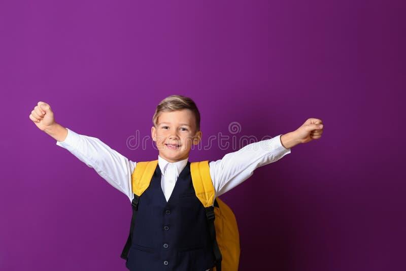 Gelukkig weinig schooljongen met rugzak op kleurenachtergrond royalty-vrije stock afbeelding