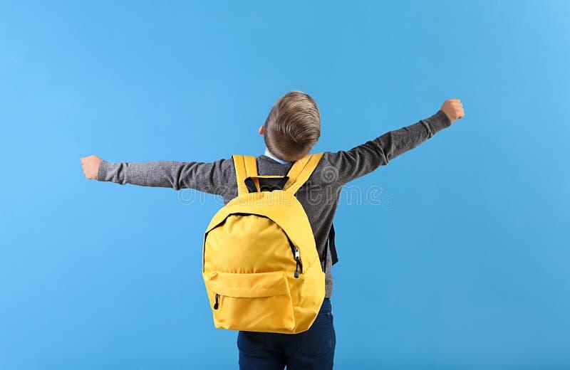 Gelukkig weinig schooljongen met rugzak op kleurenachtergrond stock fotografie