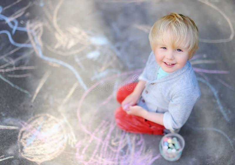 Gelukkig weinig zitting en tekening van de jong geitjejongen met kleurkrijtje op asfalt royalty-vrije stock afbeelding