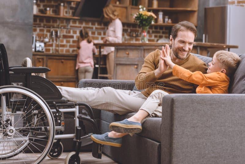 gelukkig weinig zoon met glimlachende gehandicapte vader die hoogte vijf en rolstoel status geven vector illustratie