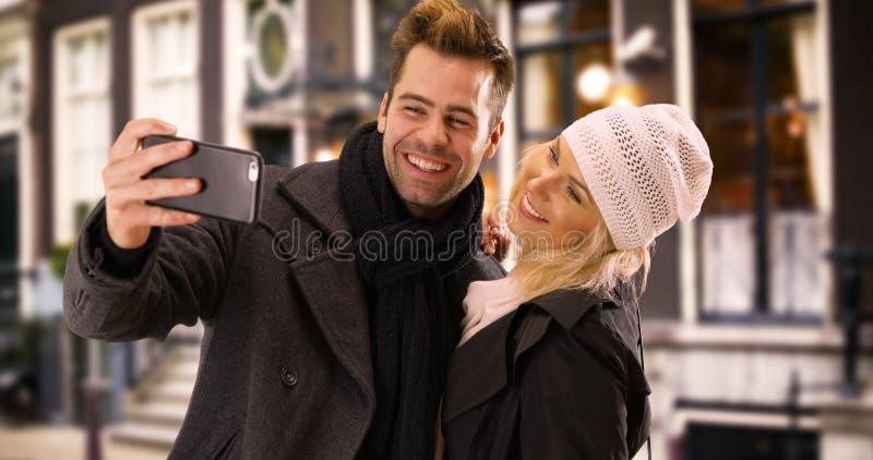 Gelukkig yucciepaar die selfies in openlucht tijdens de wintertijd nemen royalty-vrije stock foto