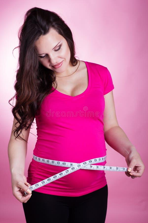 Gelukkig zwanger meisje met meetlint stock foto