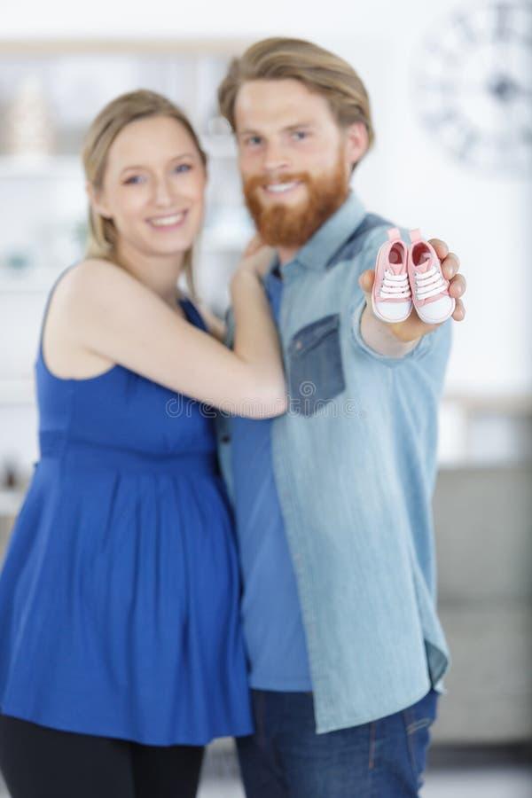 Gelukkig zwanger paar dat babyschoenen toont royalty-vrije stock foto