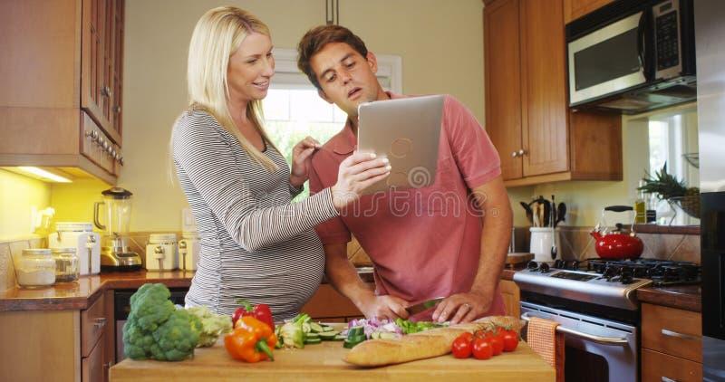 Gelukkig zwanger paar die in de keuken samenwerken royalty-vrije stock fotografie
