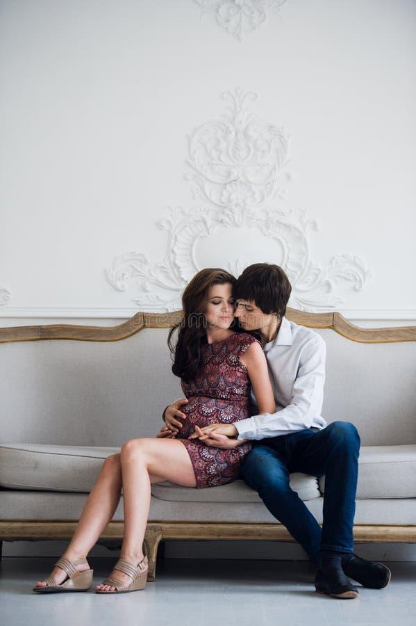 Gelukkig zwanger paar thuis, jonge het houden van familiezwangerschap, Portret van mens en vrouw die babyzitting thuis de verwach royalty-vrije stock afbeelding