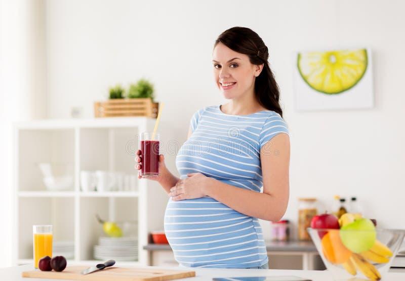 Gelukkig Zwanger vrouw het drinken sap thuis royalty-vrije stock foto
