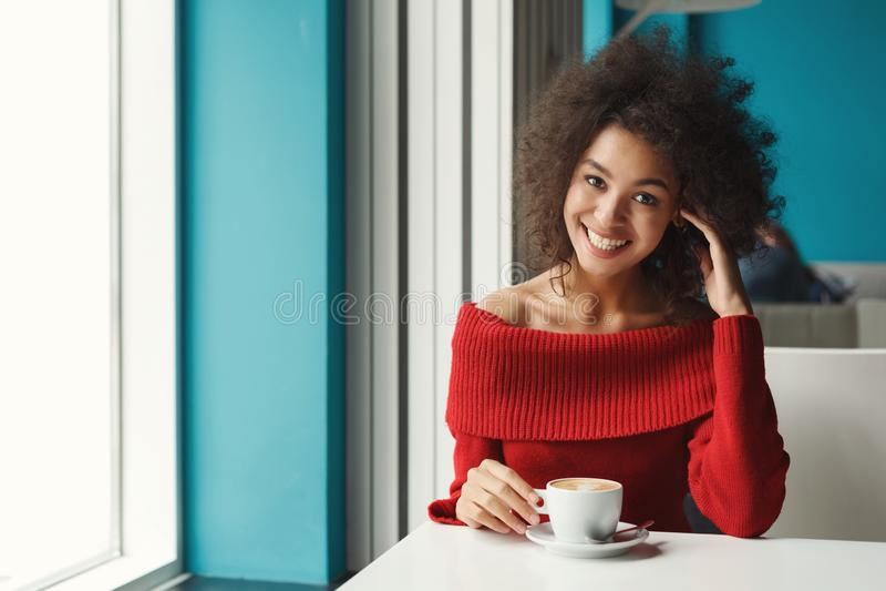 Gelukkig zwart meisje bij koffie het drinken koffie stock fotografie