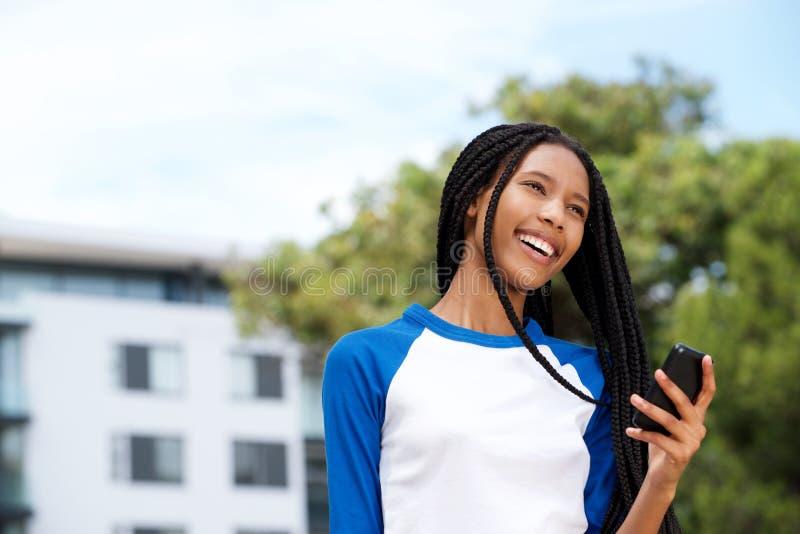Gelukkig zwart meisje die in openlucht met celtelefoon lopen royalty-vrije stock afbeelding
