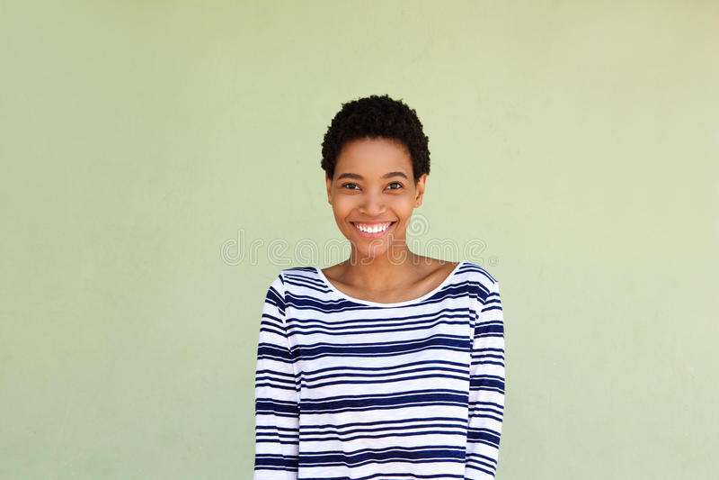 Gelukkig zwarte die in gestreept overhemd door groene achtergrond glimlachen royalty-vrije stock fotografie