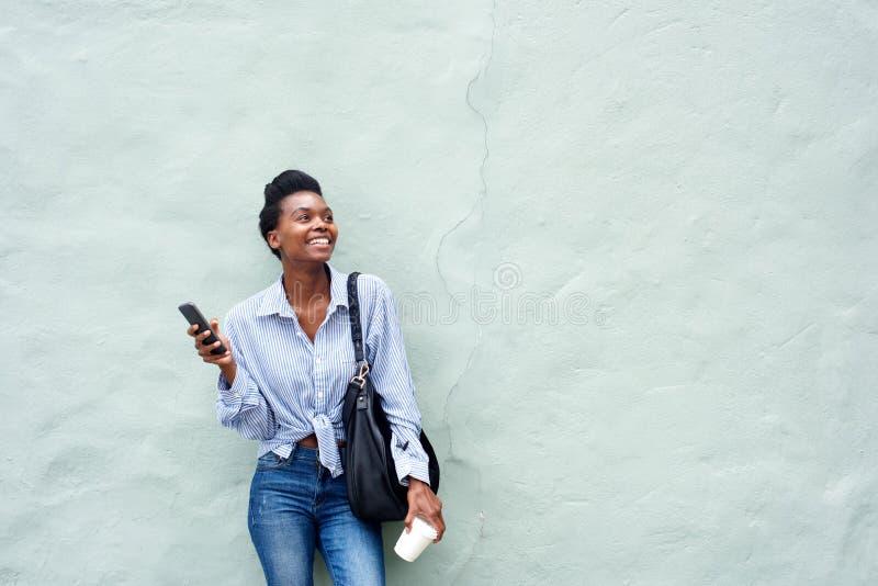 Gelukkig zwarte die mobiele telefoon houden stock afbeelding