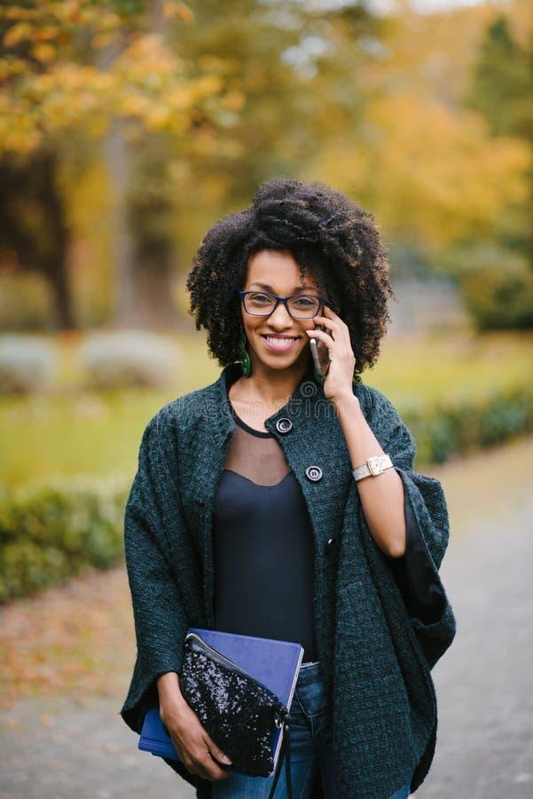 Gelukkig zwarte tijdens een mobiel telefoongesprek in de herfst royalty-vrije stock fotografie