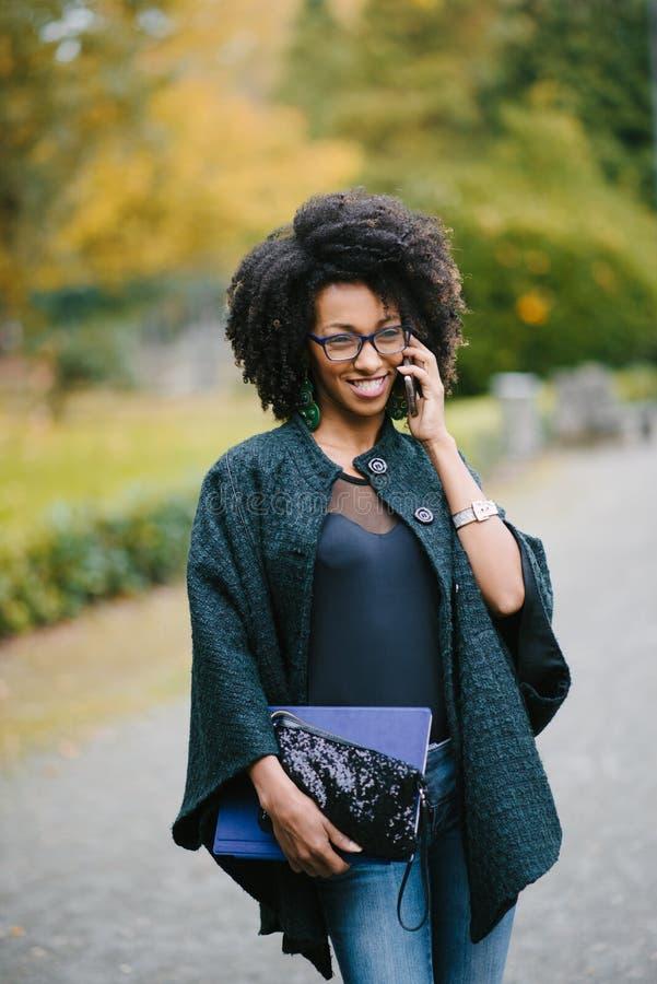 Gelukkig zwarte tijdens een mobiel telefoongesprek in de herfst stock fotografie