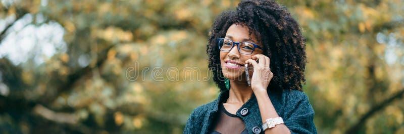 Gelukkig zwarte tijdens een mobiel telefoongesprek in de herfst royalty-vrije stock afbeelding