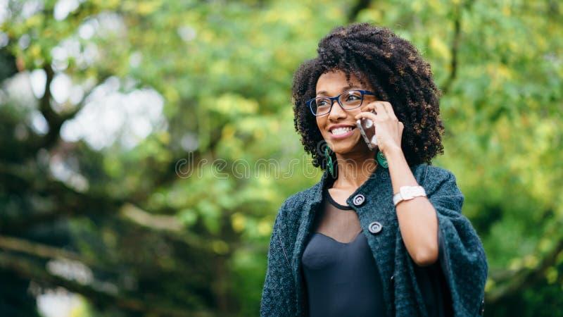 Gelukkig zwarte tijdens een mobiel telefoongesprek in de herfst royalty-vrije stock foto