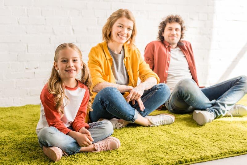 gelukkige aanbiddelijke ouders met weinig dochter die bij camera glimlachen terwijl samen het zitten stock fotografie