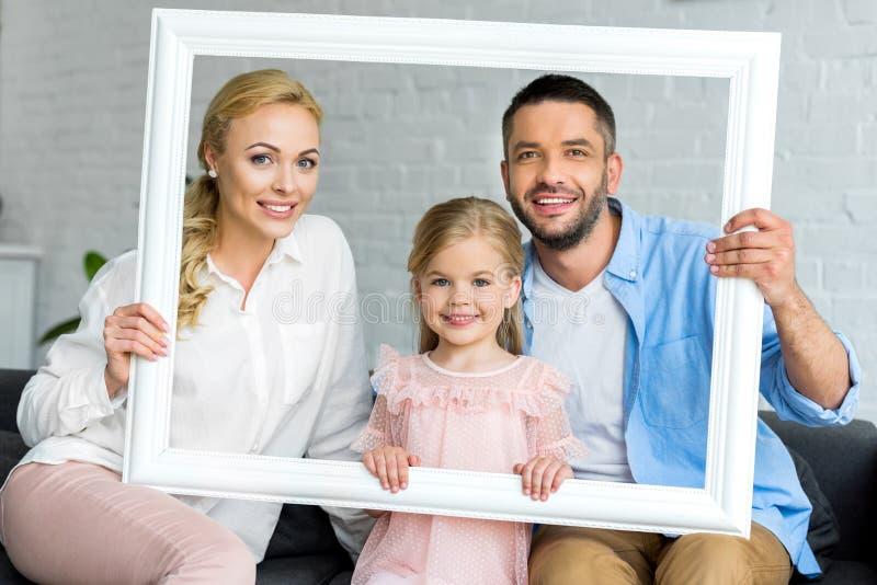 gelukkige aanbiddelijke ouders met weinig dochter die het witte kader en glimlachen houden stock foto's