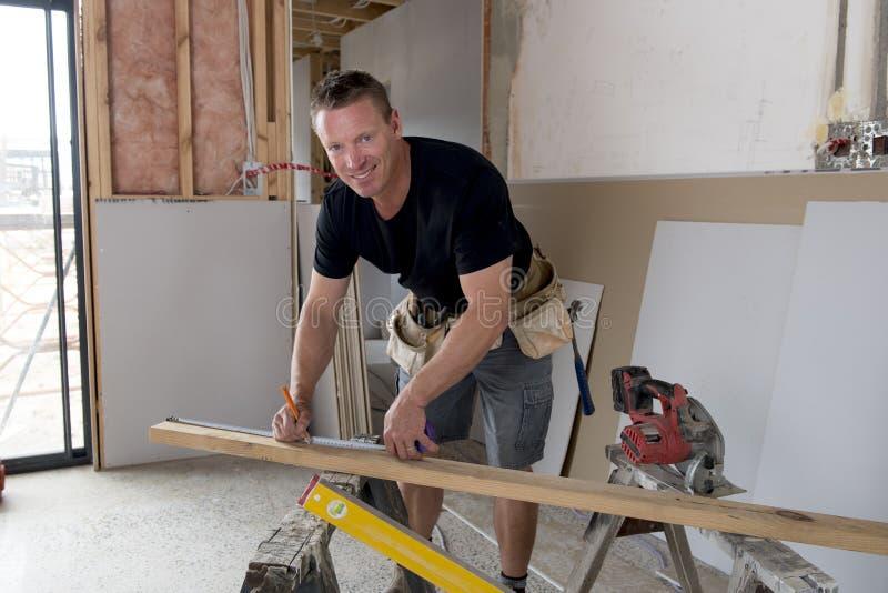 Gelukkige aantrekkelijke en zekere aannemerstimmerman of bouwersmens die en hout in industriële conc bouwbaan werken meten stock afbeeldingen