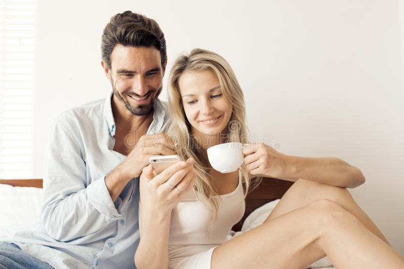Gelukkige aantrekkelijke het glimlachen paarzitting op bed in slaapkamer stock afbeelding
