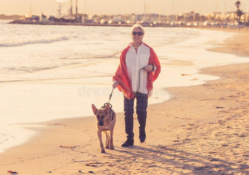 Gelukkige aantrekkelijke hogere vrouw die met haar Duitse shepardhond op het strand bij de herfstzonsondergang lopen stock foto's