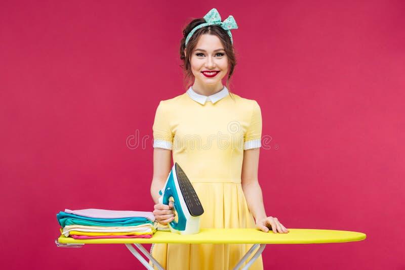Gelukkige aantrekkelijke jonge vrouw die en het strijken kleren bevinden zich stock fotografie