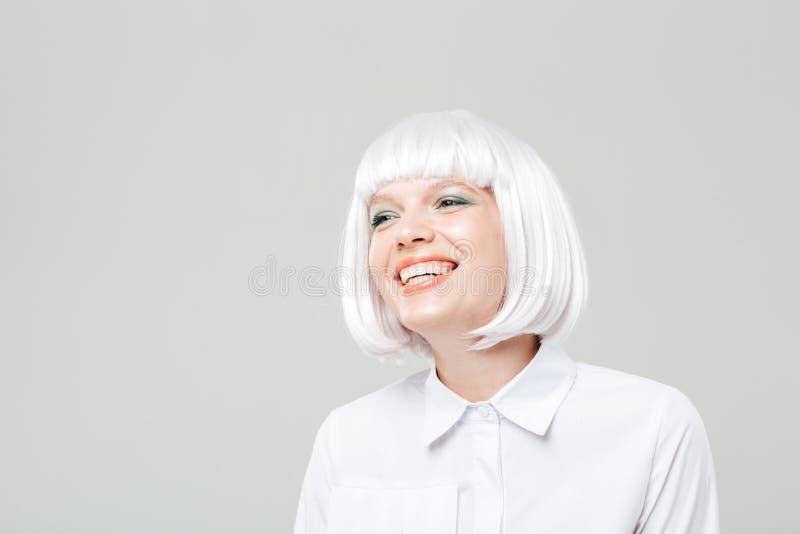 Gelukkige aantrekkelijke jonge vrouw in en blondepruik die bevinden zich lachen stock afbeeldingen