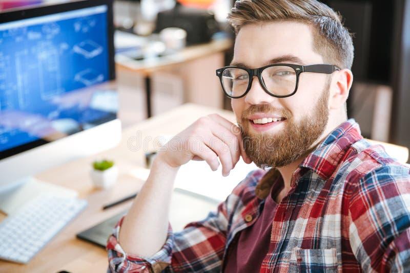 Gelukkige aantrekkelijke mens die en project op computer werken ontwerpen stock afbeeldingen