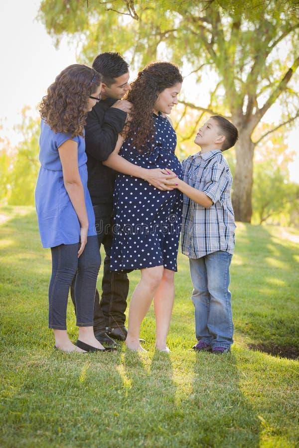 Gelukkige Aantrekkelijke Spaanse Familie met Hun Zwangere Moeder Outd royalty-vrije stock foto's