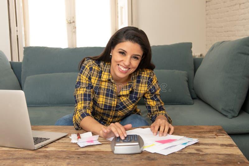 Gelukkige aantrekkelijke vrouw het berekenen huisfinanciën, betalend rekeningen die thuis calculator en laptop met behulp van royalty-vrije stock afbeelding