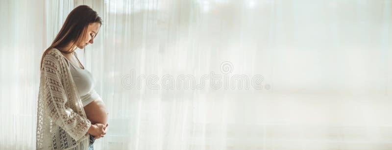 Gelukkige Aantrekkelijke zwangere vrouw die zich dichtbij het venster bevinden en haar buik houden royalty-vrije stock afbeelding
