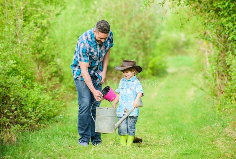 Gelukkige Aardedag Stamboom het nursering Gebruiksgieter en pot Tuinmateriaal Ecolandbouwbedrijf de kleine hulp van het jongenski stock fotografie