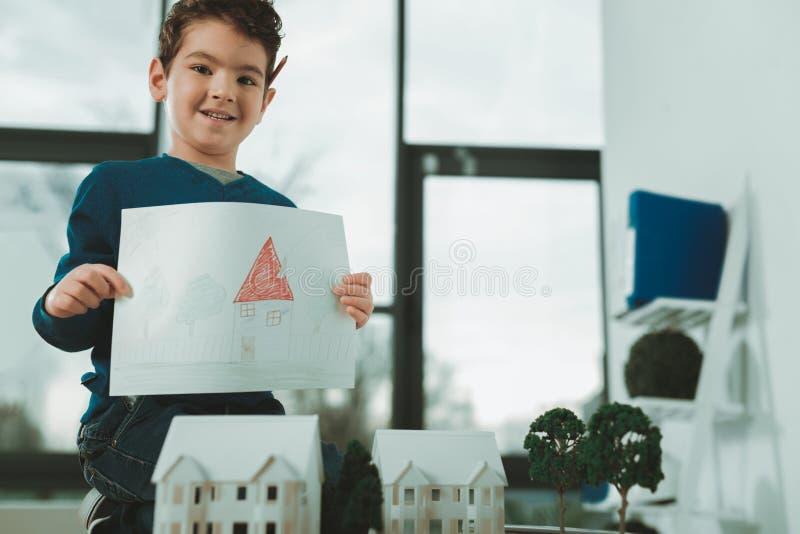 Gelukkige aardige jongen die een beeld tonen royalty-vrije stock afbeeldingen